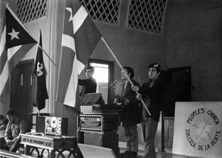 Young men holding speaking and holding flags at the Iglesia de la Gente People's Church